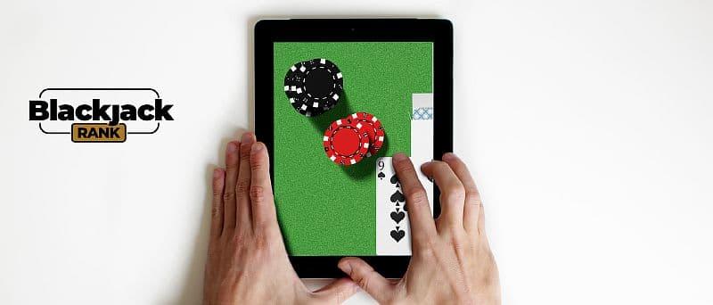Tablet in Handen mit Blackjack auf dem Bildschirm