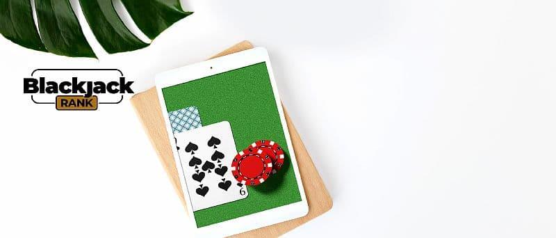 Tablet mit Blackjack auf dem Bildschirm auf einem Schneidebrett
